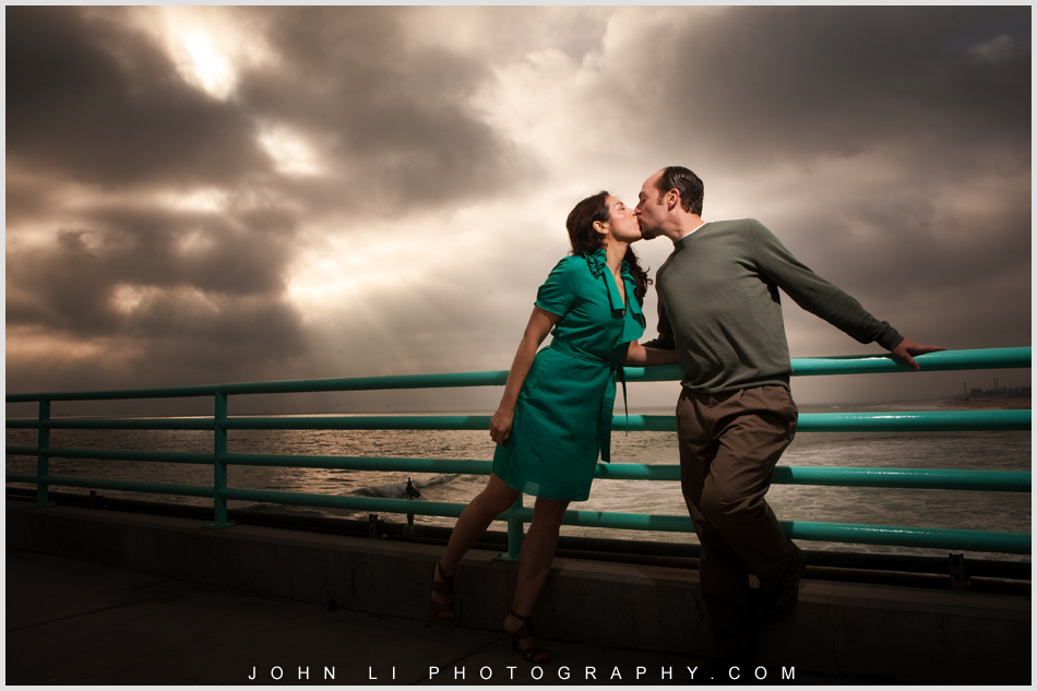 engagement in Manhattan Beach pier under Dramatic lighting