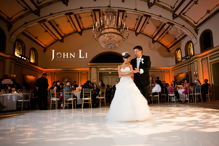 first dance in ballroom with guest in background
